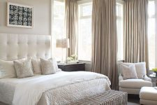 a welcoming greige bedroom with a creamy bed with a statement upholstered headboard, creamy seating furniture, a woven chest bench, greige curtains and a pendant lamp