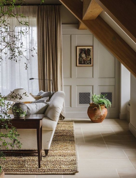 a welcoming greige living room with paneled walls, a neutral sofa, a dark stained coffee table, potted plants and a warm colored rug