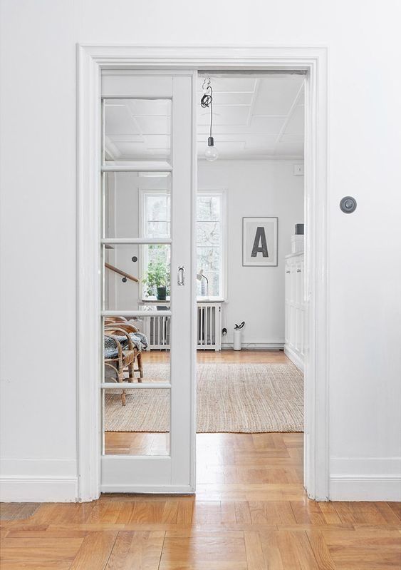 a white French pocket door separates the room and makes both spaces light-filled at the same time