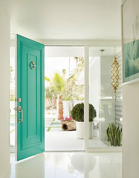 a white entrance accented with a bold green front door and gold touches are perfect for a mid-century modern house