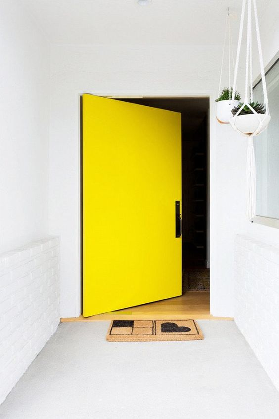 a white entrance with a concrete floor and an oversized yellow square front door are amazing to highlight the exterior of your home