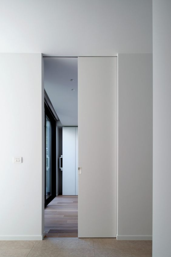 a white pocket door looks very sleek and chic and doesn't stand out from the rest of the room looking cool