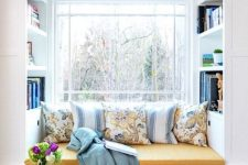 a window with a built-in storage unit with a seat, with built-in shelves and lots of pillows and a blanket is a lovely nook to read something