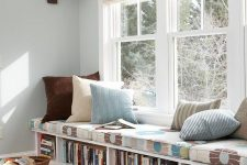 a windowsill bench with a cushion on top and a bookshelf inside it is perfect for a reading nook