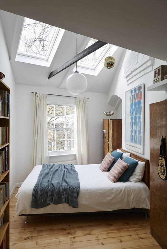 additional skylights add more natural light to this small bedroom and make it look bigger, and pendant lamps highlight the tall ceiling