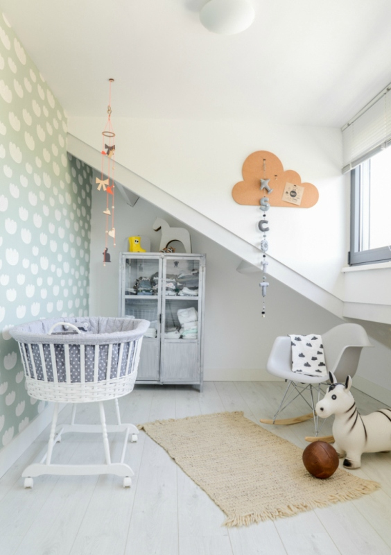 an attic Scandinavian nursery with a whitewashed wardrobe, a crib, a corcher chair, some art and a rug is fresh and ethereal