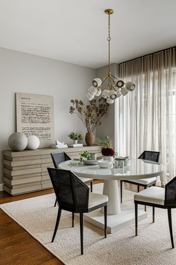 an elegant and cool greige dining room with a catchy credenza, a round table, black chairs, a cool chandelier, some rocks and potted plants