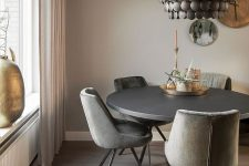 an elegant and refined greige dining room with a black round table, grey chairs, a black metal chandelier, decorative plates and a candle