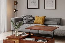 an elegant greige mid-century modern living room with a grey couch, a mini gallery wall, a pretty coffee table with a raising tabletop