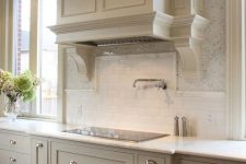 an elegant vintage farmhouse kitchen with shaker cabinets, a large matching hood, a white subway tile backsplash and white stone countertops is chic