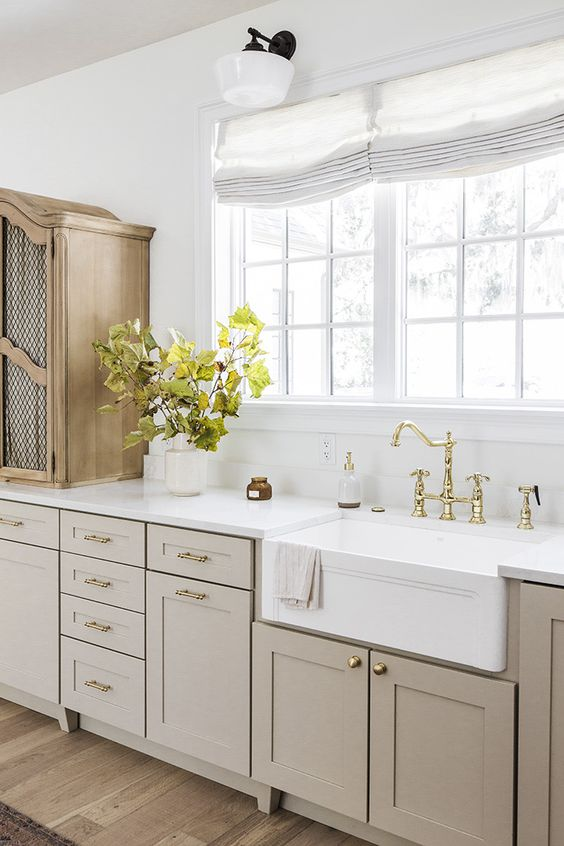 an elegant vintage greige kitchen with shaker cabinets, a white stone countertop and a backsplash, a wooden cabinet and gold fixtures