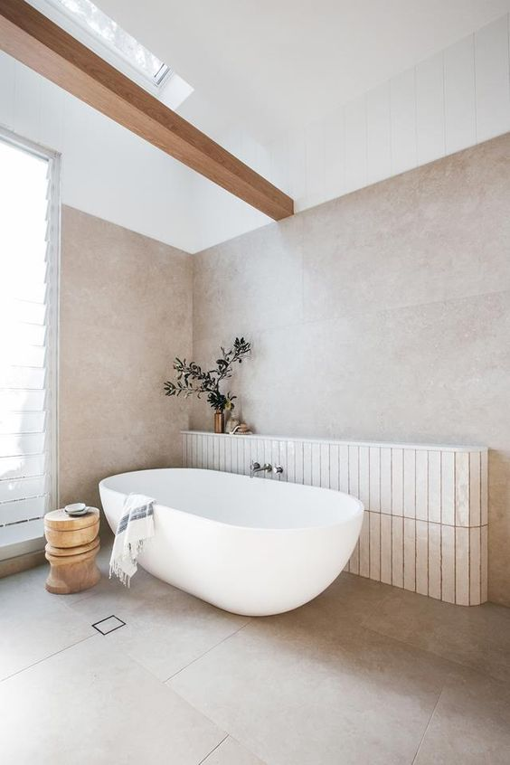 an ethereal greige bathroom with large scale tiles, a wooden beam, a window and a skylight, an oval tub and a wooden side table