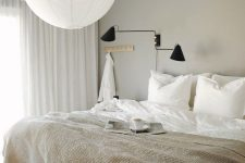 an ethereal greige bedroom with a creamy bed, a black sconce, a pendant lamp and neutral textiles is welcoming