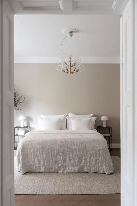 an ethereal greige bedroom with a white bed and neutral bedding, black nightstands and white table lamp plus a cool chandelier