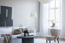 an ethereal greige living room with a white sofa and a cool wingback chair, a grey concrete round table, a floor and a pendant lamp
