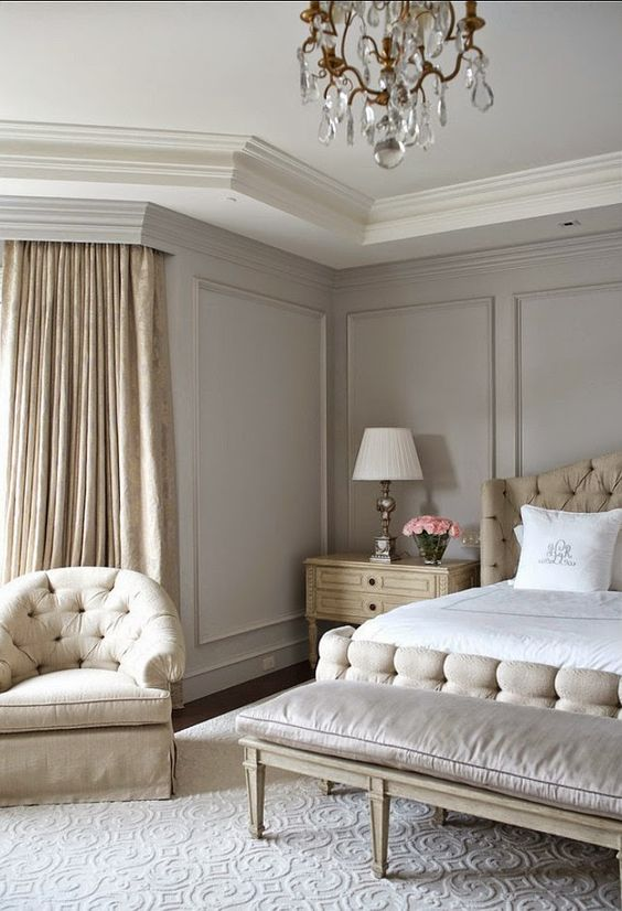 an exquisite greige bedroom with neutral upholstered furniture, a bench, neutral bedding, a crystal chandelier and tan printed curtains