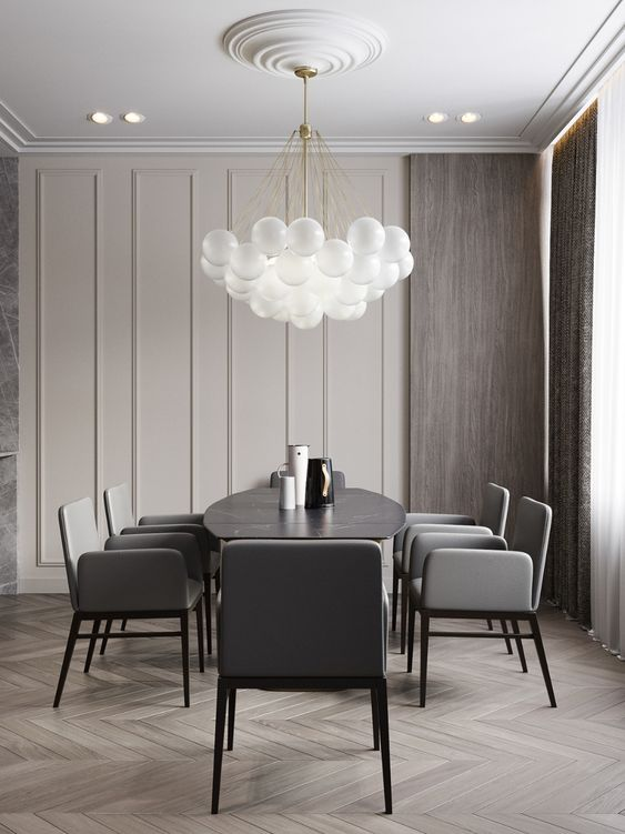 an exquisite greige dining room with paneled walls, stained wood, a black dining table, grey chairs and a bubble pendant lamp