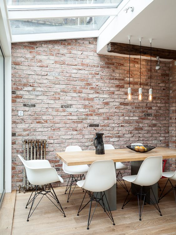 an industrial dining space with skylights is filled with daylight and pendant lamps highlight the high ceiling