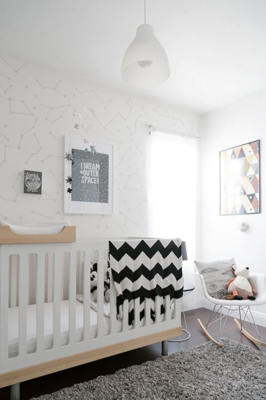 an inviting Scandi nursery with wallpaper walls, a white and stained crib, a rocker, a grey rug and some monochromatic bedding