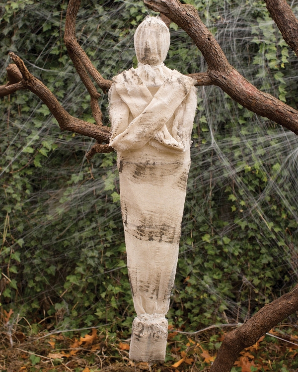 an outdoor Halloween mummy decoration is an easy and scary idea, attach on to a tree in your garden