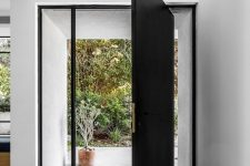 an oversized black metal front door with long and narrow windows on each side is a gorgeous solution for both a modern and a contemporary home
