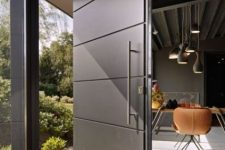an oversized blackened metal front door with a usual handle is a cool idea for a modern home and can fit soem other styles, too