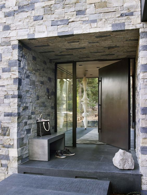 an oversized dark metal front door with a long and narrow window is a stylish idea for a modern house and it adds to the style