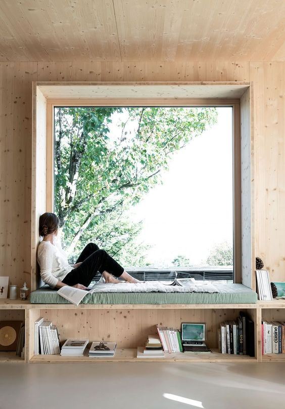 an oversized window with a built in daybed and open shelves under it is a dreamy space to read, study and just sit and dream