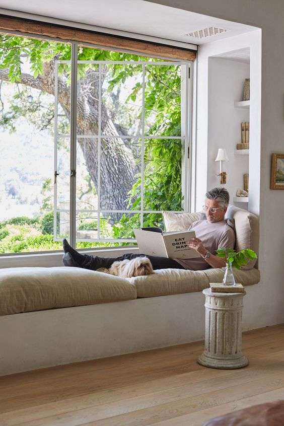 an oversized window with built in shelves, a daybed and fost and cool pillows and cushions is an ultimate nook to spend time in