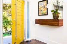 an oversized yellow planked square front door with oversized handles is a gorgeous idea for a modern or mid-century modern house
