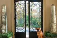 arched, wrought iron doors flanked by mirrored obelisks, with an arched window over the door and cool views of the garden through the doors