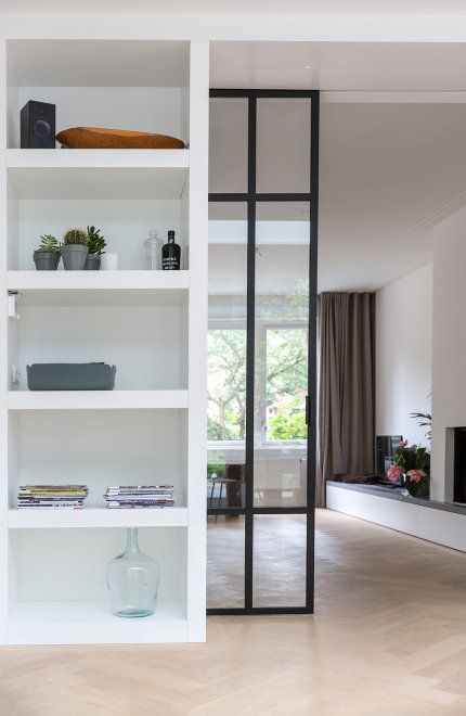 en elegant and chic black metal frame glass pocket door divides the space in a cool and stylish way without havy looks