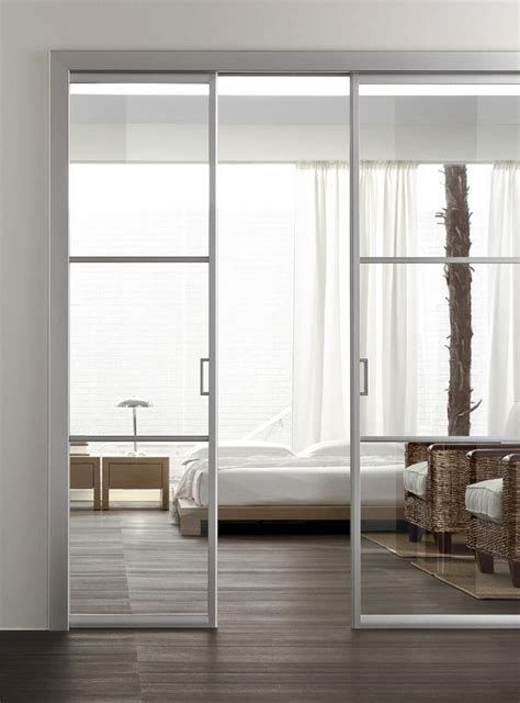 ethereal and light white white metal frame and glass pocket doors separate the bedroom from the living room in a chic way