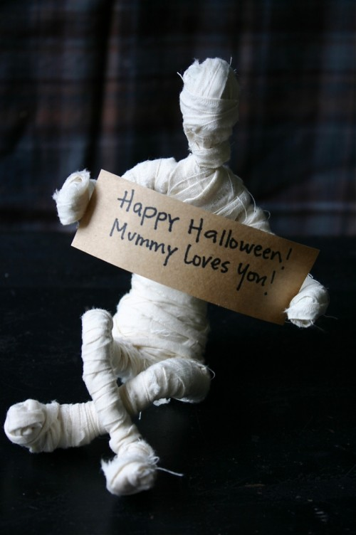 fun tabletop mummy decor with a sign is a cool idea to DIY for the coming Halloween to add a bit of fun