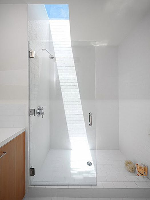 just a small skylight makes this white shower space bolder and chic and lets you enjoy sunlight as if you are having a shower outdoors