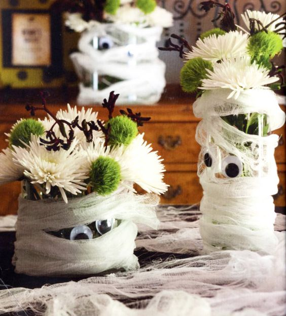 mummy-styled planters with white and green blooms are adorable as Halloween centerpieces or just decorations