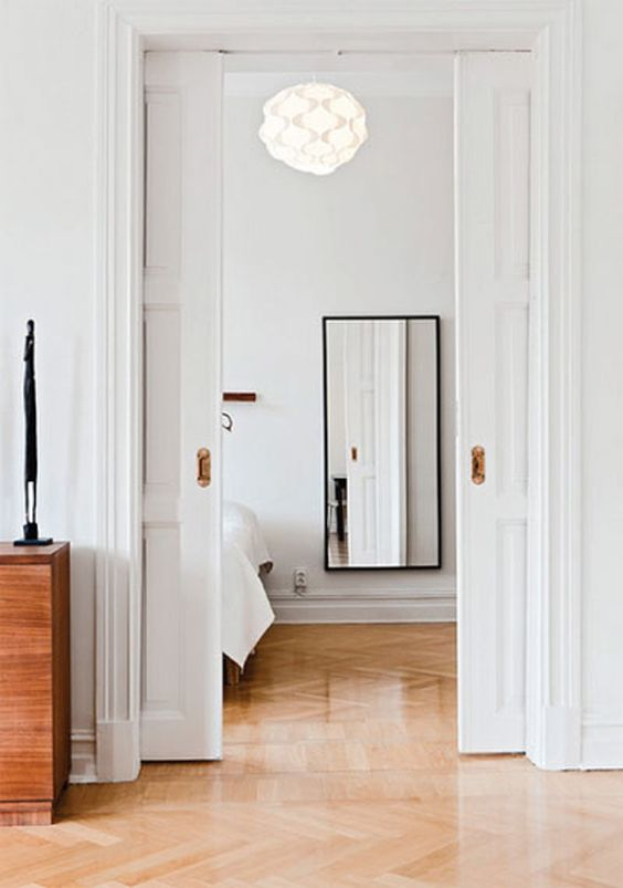 refined white paned pocket doors are a perfect way to divide the spaces in a stylish way and save a lot of room