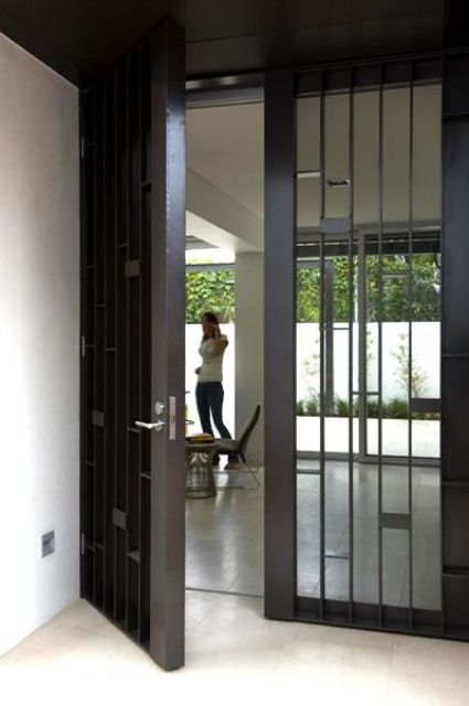 simple yet sturdy blackened steel and glass front doors are great for a modern home and they look catchy and bold