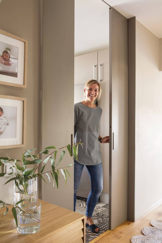 sleek and chic dove grey pocket doors wiht little handles are ideal to delicately separate the spaces without stealing room