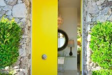 sleek bold yellow double-height doors with refined antique knobs is a gorgeous statement with both color and style of the doors