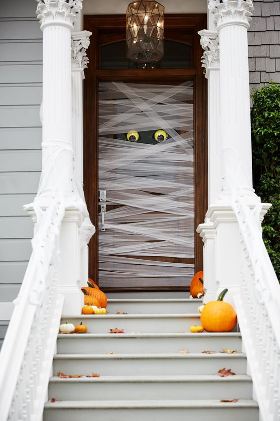 such a mummy-style front door is very easy to make, add a couple of pumpkins and fall leaves on the steps and voila - you have a Halloween porch