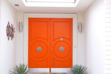 super bright orange front doors with refined vintage knobs are a great example of chic mid-century modern decor style to go for