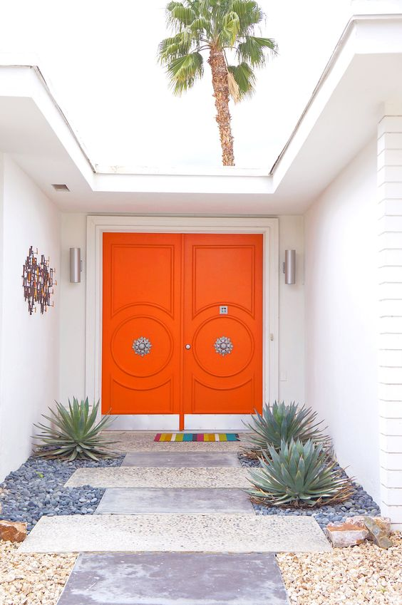 super bright orange front doors with refined vintage knobs are a great example of chic mid century modern decor style to go for
