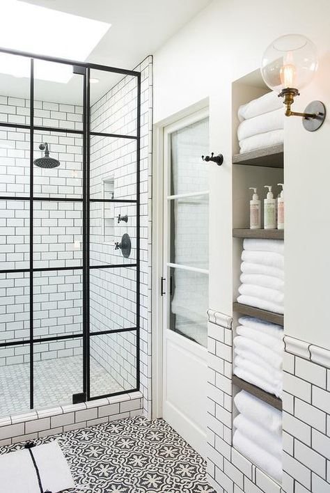 this white and black bathroom is made brighter with skylights over the shower and is filled with natural light easily