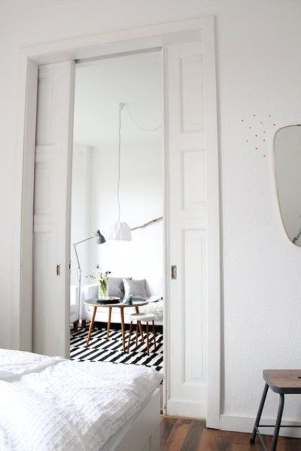 vintage-inspired white pocket doors separate the bedroom from the living room without wasting any space at all