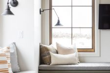 windows with built-in storage daybeds, with pillows and black sconces are amazing for reading and just enjoying the views