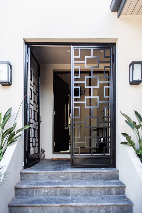 wrought metal and glass doors look modern and bold and geometry gives a nice touch to the entrance