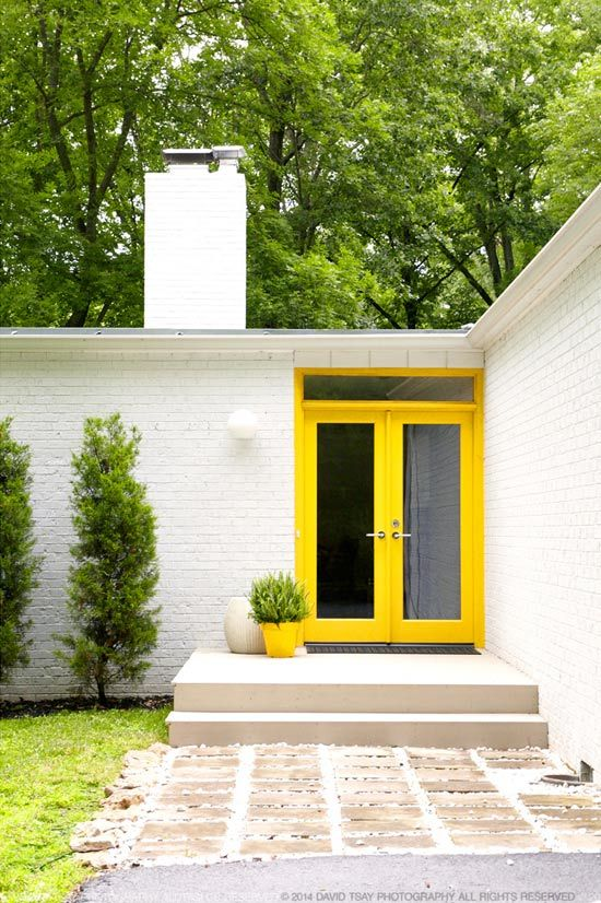 yellow glass front doors plus a yellow planter with greenery is a gorgeous idea to make the entrance of a modern house bold and cool