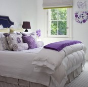 white color as the main one for bedroom decor make the space look larger and more welcoming, and bold purple add a contrasting touch to the space