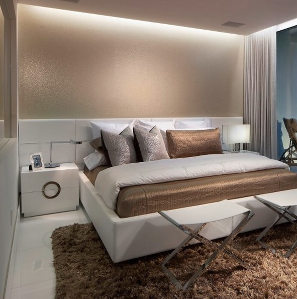 neutrals, tan and brown decor, built in lights and touches of metal make up the small bedroom larger and very luxurious